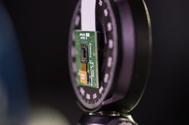 Rice University's FlatCam—the tiny chip attached to the circuit board—is a lens-less camera that may someday turn large or small surfaces into cameras. Image credit: Jeff Fitlow/Rice University
