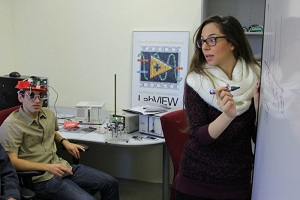 Dr. Oz Levinkron (seated), of the Technion Faculty of Medicine, wears the Technion-created device that can diagnose diseases based on eyelid motion. At right is lead researcher Adi Hanuka, of the Technion's Andrew and Erna Viterbi Faculty of Electrical Engineering. Source: American Technion Society