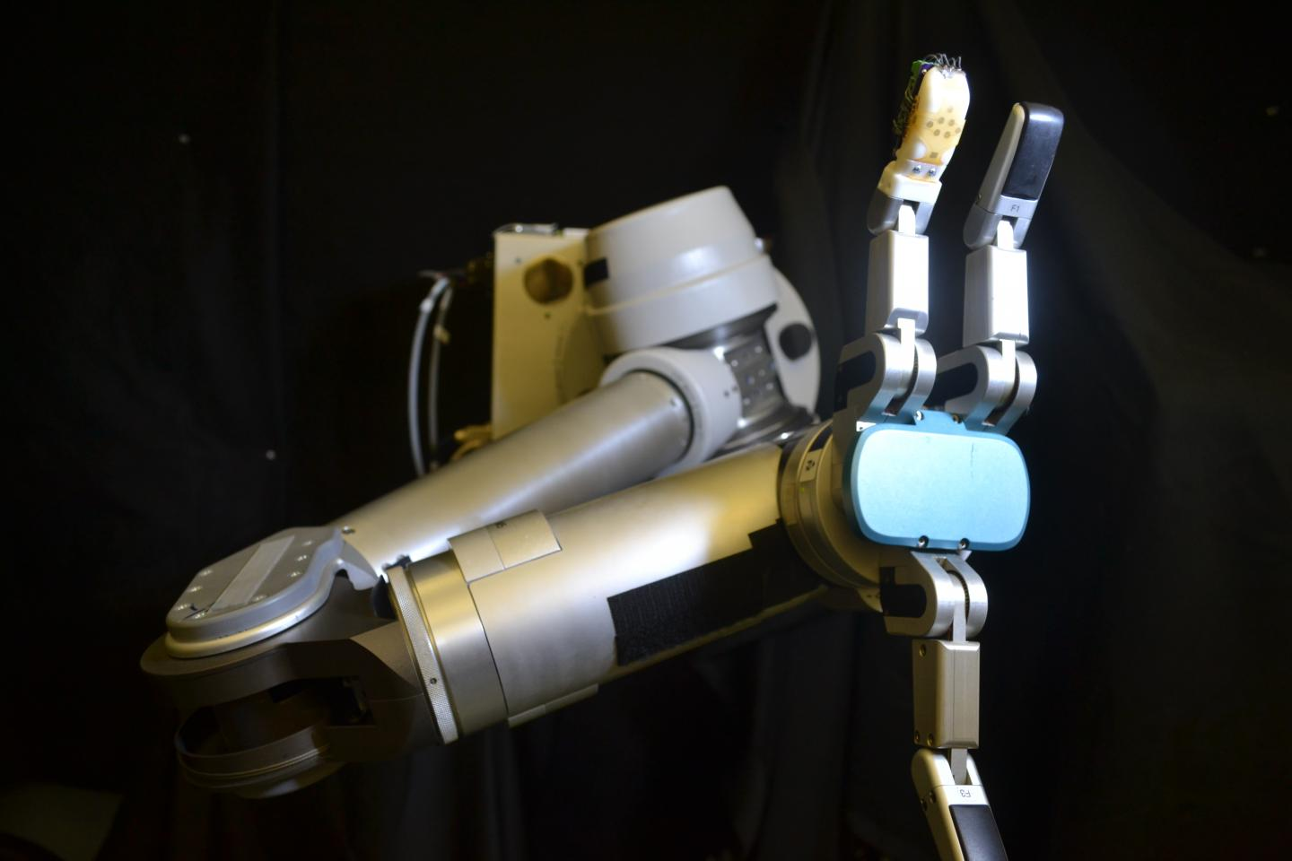 The flexible sensor skin wrapped around the robot finger (orange) is the first to measure shear forces with similar sensitivity as a human hand -- which is critical for successfully gripping and manipulating objects. (UCLA Engineering)