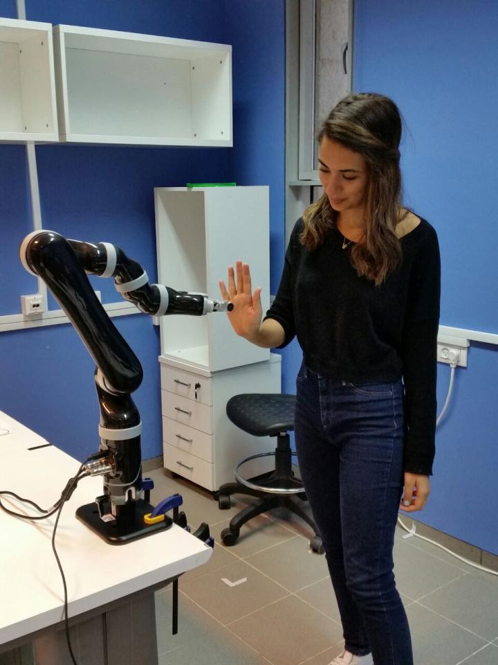 Ben-Gurion University of the Negev student researcher Shir Kashi interacts with robotic arm as part of her research in personalizing human-robot interactions to develop an interactive movement protocol for rehabilitation. (Ben-Gurion U. Israel)
