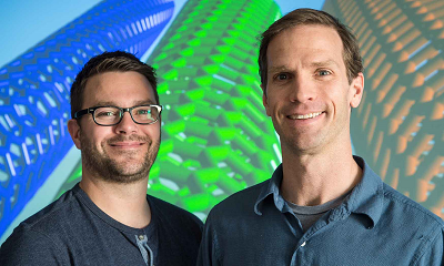 NREL scientists Andrew Ferguson, left, and Jeffrey Blackburn stand in front of a screen displaying single-walled carbon nanotubes. (Photo by Dennis Schroeder/NREL)