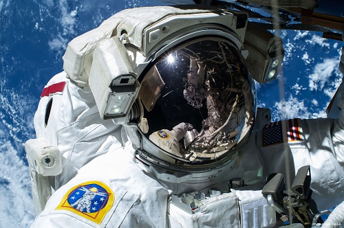 "Astronaut Barry ""Butch"" Wilmore during a spacewalk on Feb. 21, 2015, as the Earth's surface passes by in the background. (Source: NASA)"