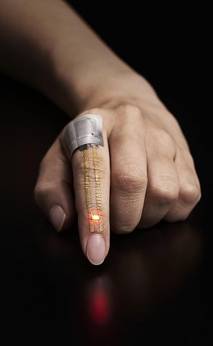 The electric current from a flexible battery placed near the knuckle flows through the conductor and powers the LED below the fingernail. Source: University of Tokyo