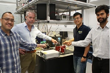 Researchers David Marpaung, Benjamin Eggleton, Yang Liu and Amol Choudhary pointing at a thumbnail-size chip being evaluated in the broadband microwave testbed, inside the Sydney Nanoscience Hub. Image credit: University of Sydney