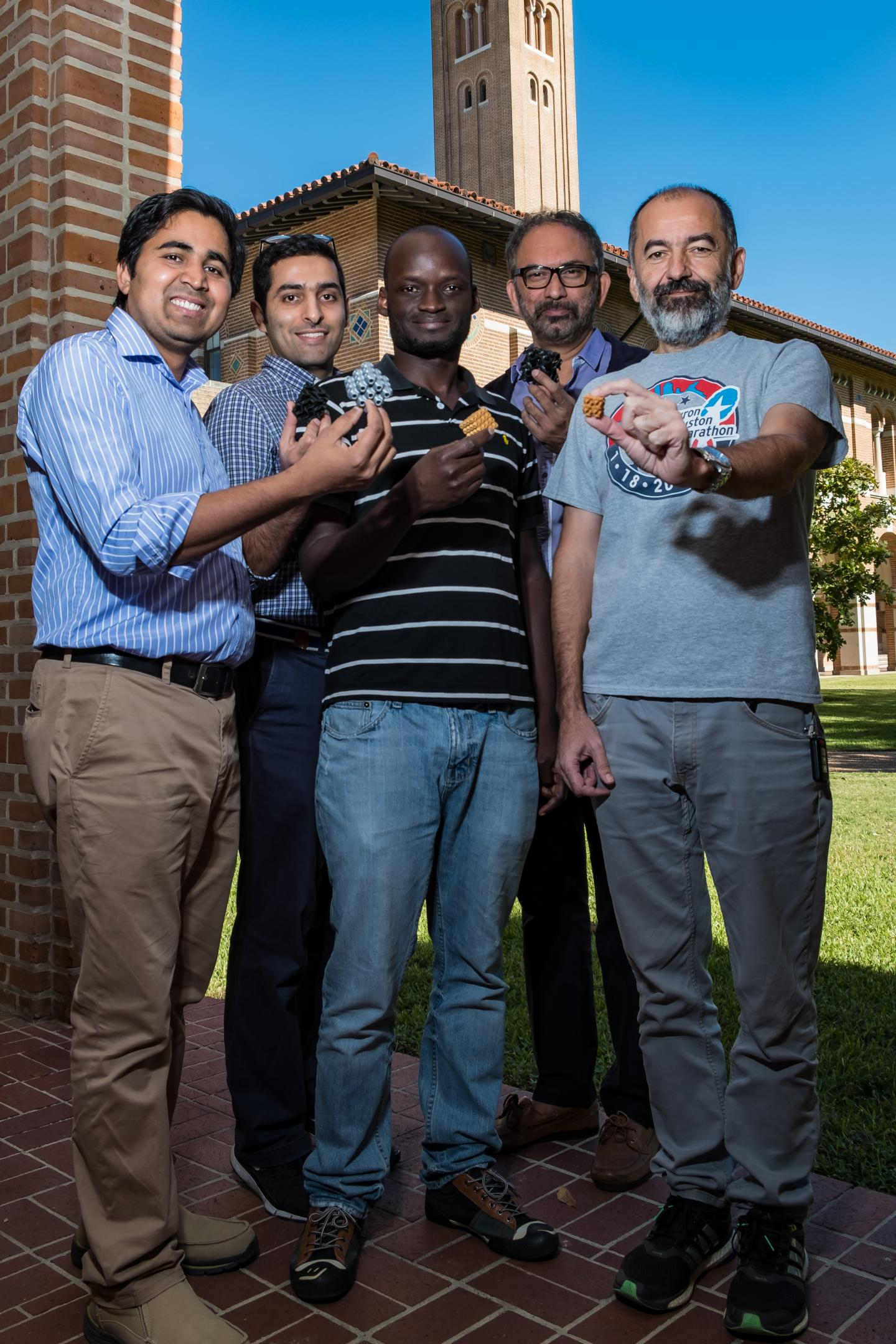 From left, Rice University researchers Chandra Sekhar Tiwary, Seyed Mohammad Sajadi, Peter Owuor, Pulickel Ajayan and Robert Vajtai hold samples of 3-D printed schwarzites, porous blocks based on complex mathematical models created in the 19th century and further developed in the 20th. The materials retain their strength at any scale, from the nano to the macro. (Jeff Fitlow/Rice University)