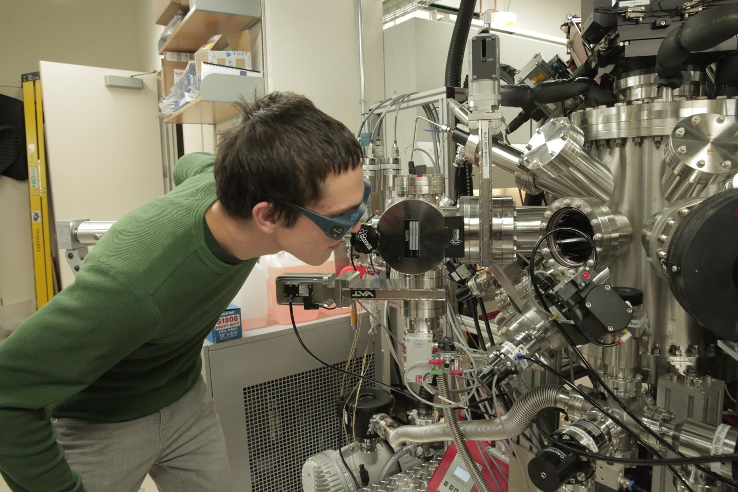 Physics graduate student Julian Irwin checks equipment in the lab of materials science and engineering Professor Chang-Beom Eom, where researchers have produced a material that could exhibit the best qualities of both solid-state and spinning disk digital storage. Source: SARAH PAGE