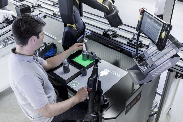 A worker uses Bosch's concept workstation for industrial automation that contains a robot assistant. Image credit: Bosch