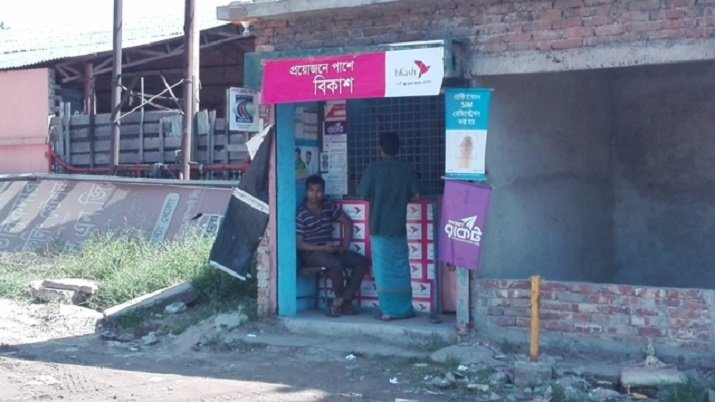 Any hole in the wall can be converted into a SIM card recharge center. Shops and kiosks like these are common around many parts of Asia; this one happens to be in Bangladesh.