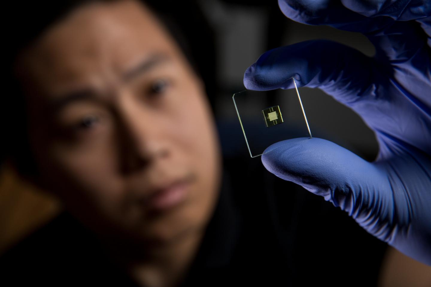 Hua Gong, a Ph.D. student at BYU, holds up a 3-D-printed microfluidic device. (Source: BYU)