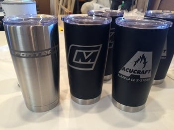 Figure 1: Example mug designs. Stainless steel (left) created by sandblasting; black mugs (right) created by laser engraving. (Source: Laser Custom Creations)