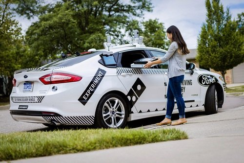 A customer receives a pizza from an autonomous delivery vehicle. Source: Ford