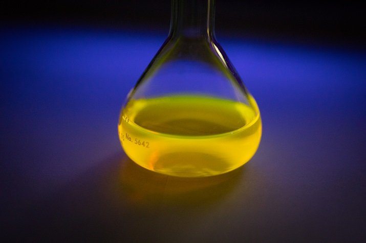 The glowing solution of dye under a black light that could be used in large-scale rechargeable energy-storage batteries. Source: University of Buffalo