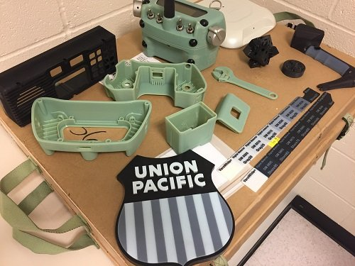 All of these parts were produced using UP's 3-D printer including the black panel which is used to house an in-cab train radio system. (Source: Union Pacific)