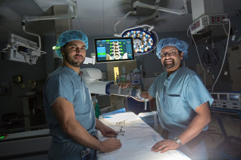 Henry Ford Allegiance Health neurosurgeons Azam Basheer, M.D., (left) and Amritraj Loganathan, M.D., with the ExcelciusGPS robot. (Source: Henry Ford Allegiance Health)