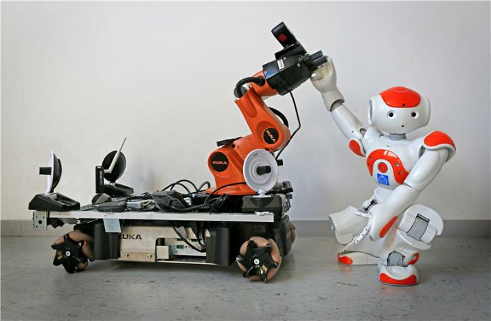 Two off-the-shelf robots demonstrate how robots can pick up each other's signals for assistance. (Image Credit: KTH Royal Institute of Technology)