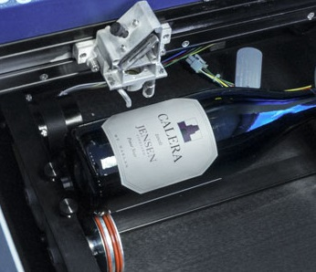 Figure 5: The rotary attachment allows for cylindrical items such as wine bottles, glasses or flashlights for engraving. (Source: Epilog Laser)
